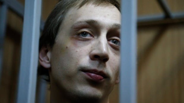 Pavel Dmitrichenko looks through bars as he stands in a Moscow court room in Oct. 2013. The Bolshoi dancer and two accomplices who organized an acid attack against the ballet's artistic director, Sergei Filin, saw their prison sentences shortened.