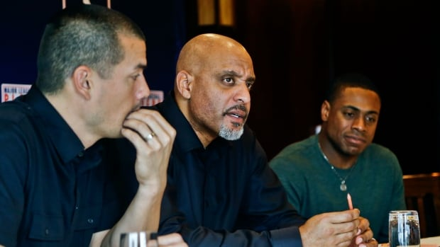 Tony Clark, the newly named Executive Director of the Major League Baseball Players Association, centre, sits with Curtis Granderson, right, and Jeremy Guthrie, left, as he answers questions during a news conference at the organizations' annual meeting on Tuesday.