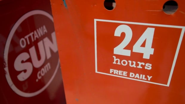 A 24 hours newspaper box sits beside an Ottawa Sun box in Ottawa. Sun Media Corp. is cutting about 200 jobs across the company,