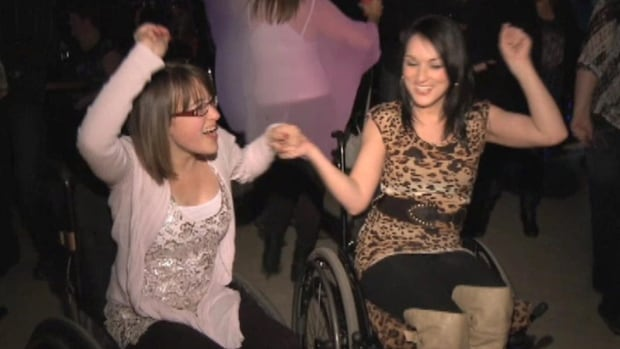 Janica and Jacinda Hodder, who both live with an undiagnosed medical condition, dance in their wheelchairs at a fundraising event to send Jacinda for American medical treatment.