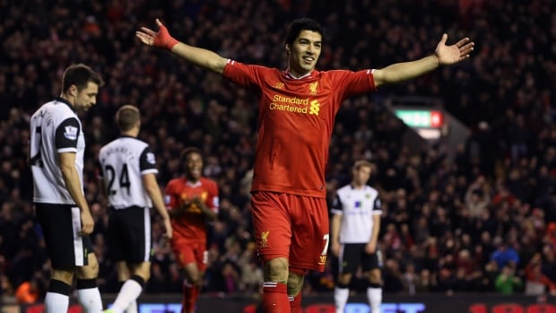 Luis Suarez celebrates the goal of teammate Raheem Sterling during the Barclays Premier League match between Liverpool and Norwich City at Anfield on December 4, 2013 in Liverpool, England. Suarez finished the match with four goals.