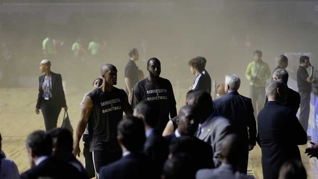 Minnesota Timberwolves players leave as smoke engulfs the basketball court against the San Antonio Spurs in Mexico City on Wednesday.
