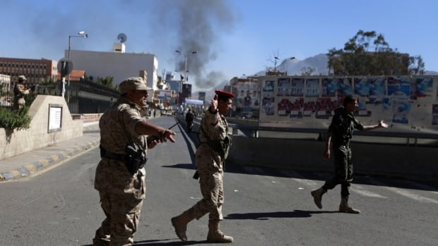 Yemeni soldiers gesture along a road leading to the Defence Ministry's compound in the capital Sanaa after an attack that killed at least 18.