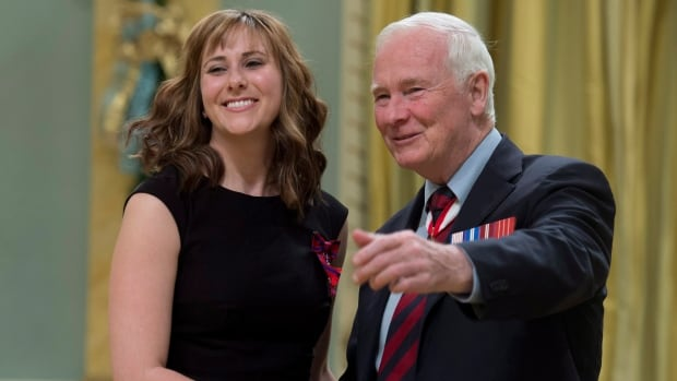 Flight attendant Nicole Louise Foran, left, is presented the Star of Courage by Governor General David Johnston during a ceremony at Rideau Hall.