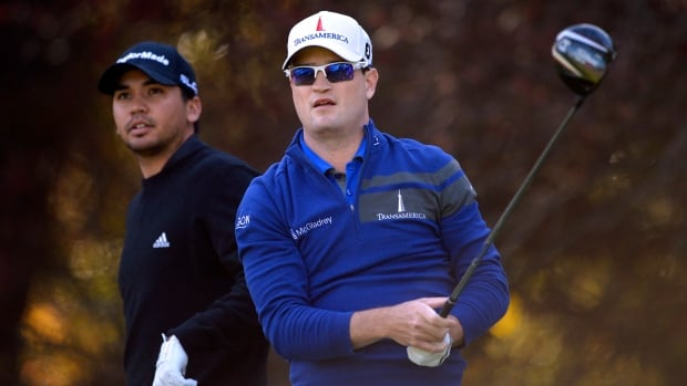 Zach Johnson, right, tees off on the second hole as Jason Day watches during the first round of the Northwestern Mutual World Challenge at Sherwood Country Club on Thursday in Thousand Oaks, Calif.
