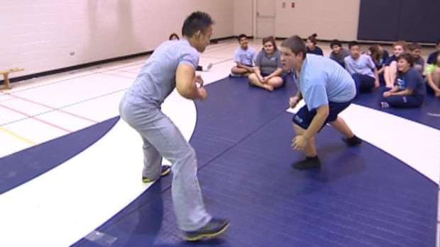 Student Drayden Cyr wrestles with graduate support worker Ron Gonzales at Mother Teresa Middle School.
