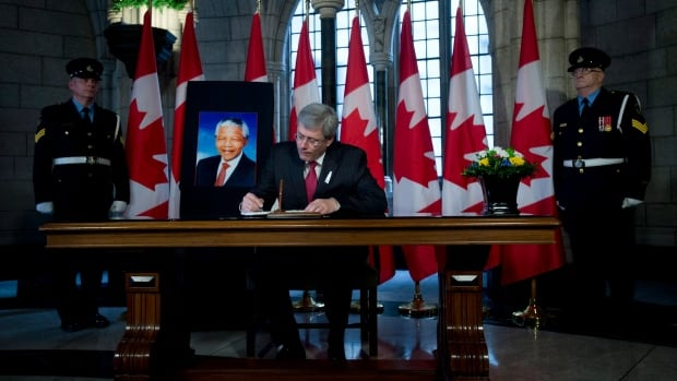 Prime Minister Stephen Harper signs a book of condolence for Nelson Mandela on Parliament Hill in Ottawa.