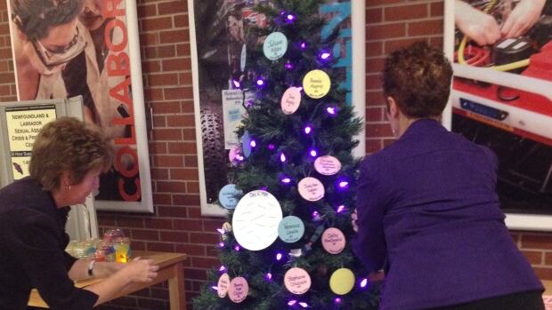 Debbie Hibbs, the mother of murder victim Juliane Hibbs, and Connie Pike of the Coalition Against Violence, hang ornaments with the names of murdered women on a tree at Memorial University's engineering building.