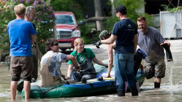 Residents and volunteers take a break in a raft as the neighbourhood of Bowness recovered after flooding in June.