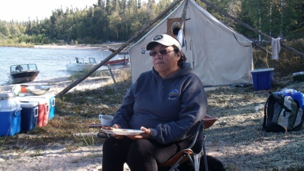 "Alice Rigney, Athabasca Chipewyan FN,  picking berries on Burntwood Island, Lake Athabasca.  ""They say oil is development and progress, but for me it's not, it's destruction."""