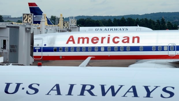 An American Airlines plane between two US Airways planes at Washington's Ronald Reagan National Airport. Their merger is complete today as American Airlines emerges from bankruptcy.