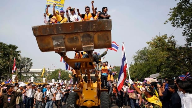 Anti-government protesters shout slogans on Monday after removing concrete barricades from outside Government House, which houses Prime Minister Yingluck Shinawatra office, in Bangkok, Thailand.