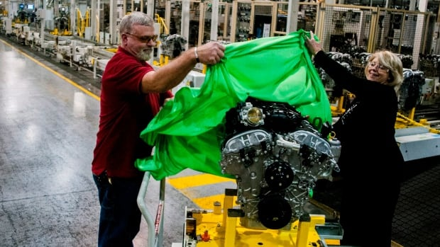 Loyd Hargis , Jr., left, and Terri Burden, Flint Engine plant manager, unveil a 3.6-litre, 302 horsepower (224 kW) V6 engine, which is being produced at GM's Flint Engine. The government bailout of GM is estimated to have saved one million jobs.