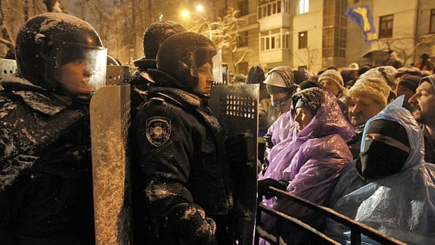 Riot police gather near a barrier set up by Ukrainian supporters of EU integration in central Kiev on Monday. President Viktor Yanukovych is looking for ways to defuse the three-week-old crisis.