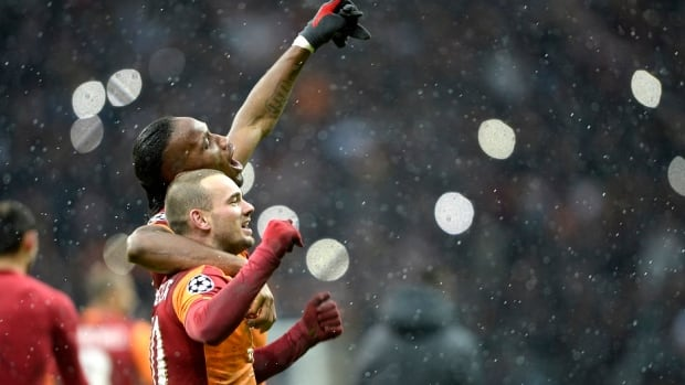 Wesley Sneijder, front, and Didier Drogba celebrate Galatasaray's 1-0 victory over Juventus.  The win pushes Galatasaray into the knockout stage of the Champions League.