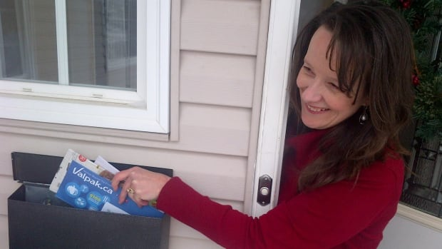 Mill Woods resident Charmayne Khan gets her mail Wednesday morning.  Door-to-door delivery in Edmonton will be phased out within the next five years.