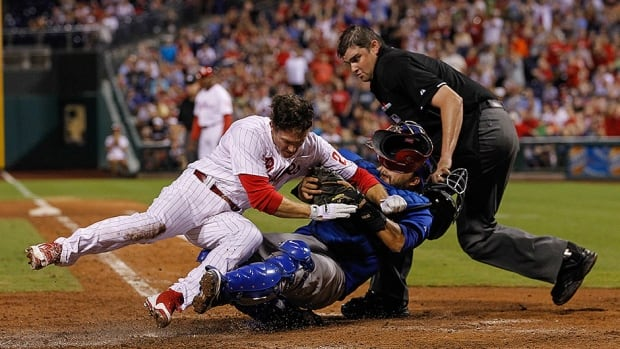 Chase Utley, left, of the Philadelphia Phillies collides with Dioner Navarro, right, seen here with the Chicago Cubs, on August 7, 2013.  Navarro was carted off the field and taken to hospital.