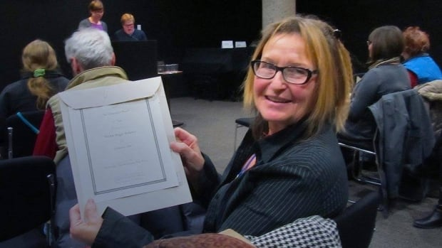 Helma Rogge Rehders proudly displays her poetry award