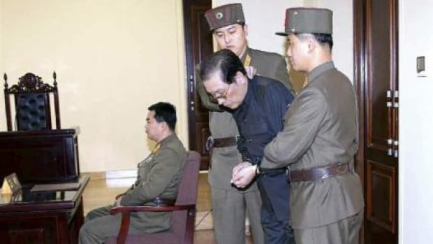 Jang Song Thaek, with his hands tied with a rope, is dragged into court by uniformed personnel in this picture taken from Rodong Sinmun December 12, 2013 and released by Yonhap.