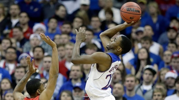 Kansas' Andrew Wiggins, right, shoots over New Mexico's Arthur Edwards (5) during the second half of an NCAA college basketball game on Saturday in Kansas City, Mo.