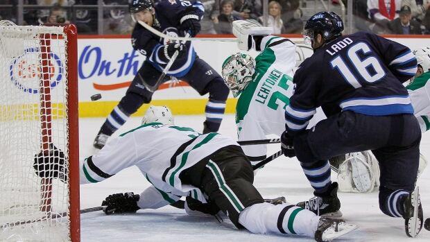Winnipeg Jets' Blake Wheeler (26) scores his second goal against Dallas Stars' Jamie Oleksiak (5) and goaltender Kari Lehtonen (32) as Jets' Andrew Ladd (16)v�looks on during second period NHL action in Winnipeg on Saturday, December 14, 2013. THE CANADIAN PRESS/John Woods