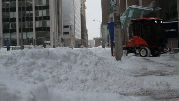 A Bobcat snow plow clears the sidewalk along Queen Street in front of the World Exchange Plaza in Ottawa as snow piles up in one of the street's lanes.