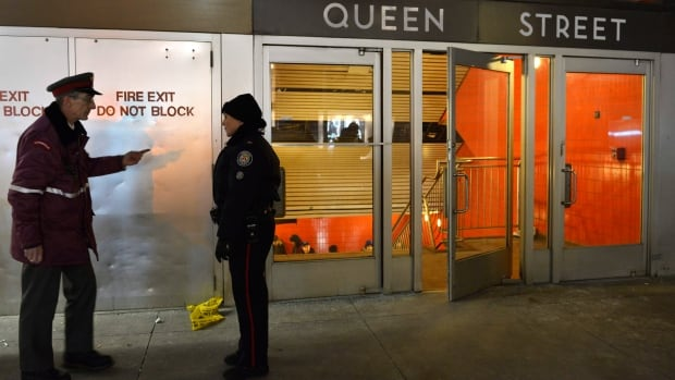 A TTC employee talks with a police officer at the Queen Street subway station entrance in Toronto on Friday Dec. 13, 2013.