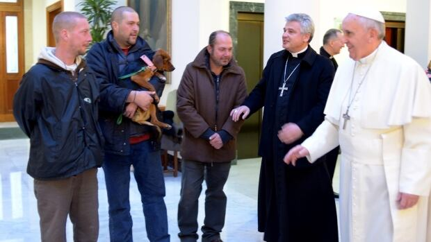 Pope Francis and Archbishop Konrad Krajewski welcome homeless men at the Vatican to celebrate Francis's 77th birthday.