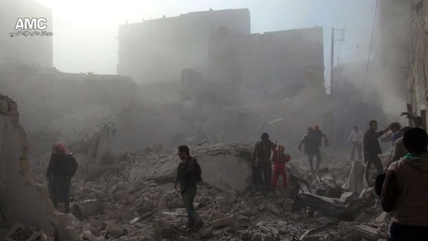 Syrians inspect the rubble of damaged buildings following a Syrian government airstrike in Aleppo. Syrian warplanes dumped explosives-laden barrel bombs over opposition-held parts of the northern city on Wednesday, the fourth day of a relentless offensive.