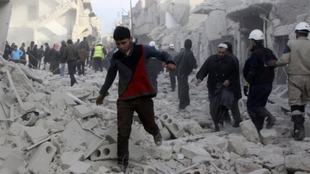 People run on debris at a site hit by what activists said was an airstrike from forces loyal to Syria's President Bashar al-Assad in the Tareek Al-Bab area of Aleppo in December, 2013. Assad's government and the opposition have agreed to consider opening humanitarian access ahead of a peace conference, according to top diplomats from U.S. and Russia.