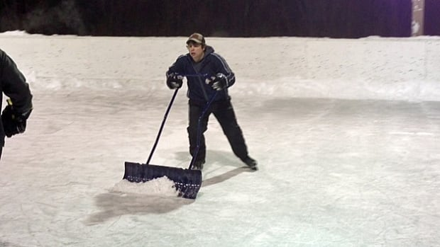 A Sudbury youth helps out with cleaning off the ice at a rink in Azilda.