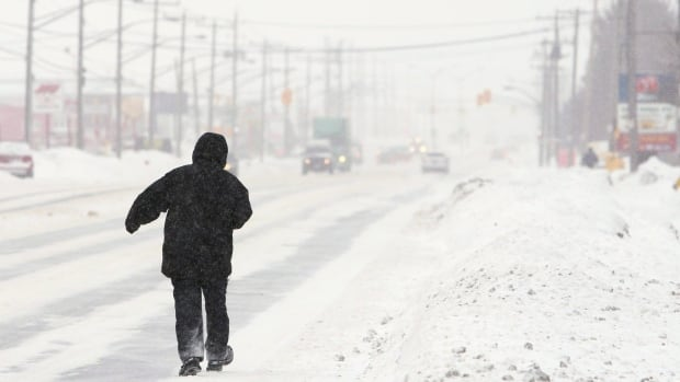 A man walks along a snow-covered Dundas Street in London, Ontario, Wednesday, February 2, 2011, after the area was hit by a winter blizzard overnight.