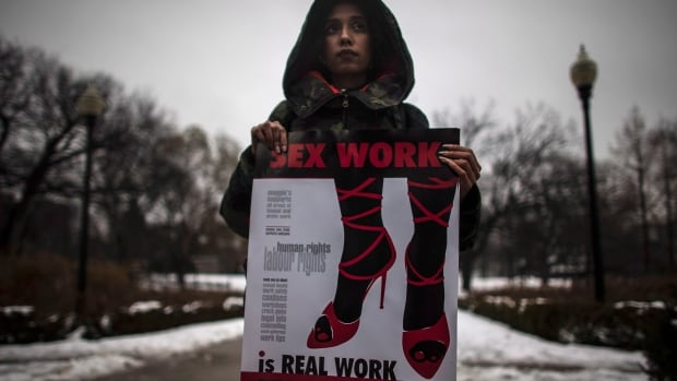 A woman (who requested to withhold her name) holds a sign during a rally to support Toronto sex workers and their rights on Dec. 20. Canada's Supreme Court struck down prostitution laws last year and gave Parliament a year to produce new legislation. The proposed bill, C-36, doesn't define sexual services.