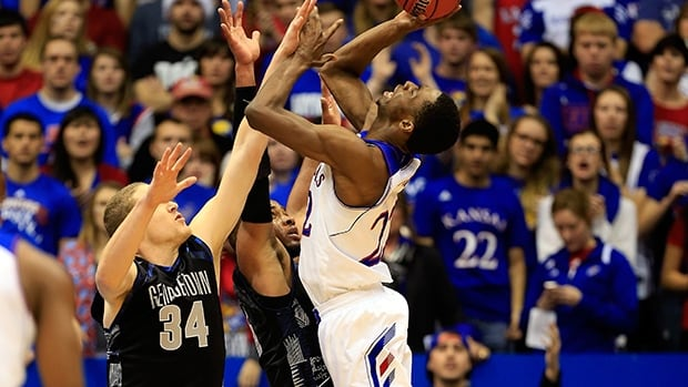Andrew Wiggins of the Kansas Jayhawks is fouled by Nate Lubick of the Georgetown Hoyas on December 21, 2013 in Lawrence, Kansas.