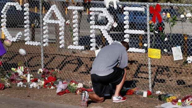 Parker Semin, a graduate of  Arapahoe High School, prays at a makeshift memorial bearing the name of student Claire Davis, a few days after she was shot by a classmate on Dec. 13, 2013.