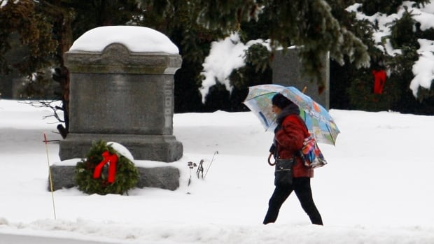 A visitor walks through the snow at Mount Pleasant Cemetery in Toronto onDecember 21, 2013. Environment Canada is forecasting a major ice storm in Southern Ontario this evening into Sunday morning.