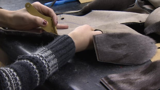 An employee of Always In Vogue in St. John's makes a pair of seal skin mittens to sell at the store. The owner of the shop says business has been seriously booming since Pamela Anderson and Sam Simon visited the province to ask sealers to retire.