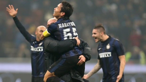 Inter Milan defender Yuto Nagatomo, top, hugs teammate Esteban Cambiasso at the end of their match against AC Milan at the San Siro stadium in Milan, Italy on Sunday.