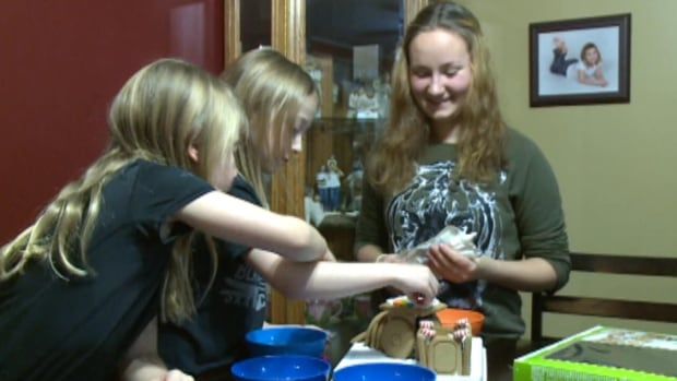 Swiss exchange student Madlaina Stucher, far right, shows the two Stuckless children how to make a gingerbread house as part of her Christmas traditions.