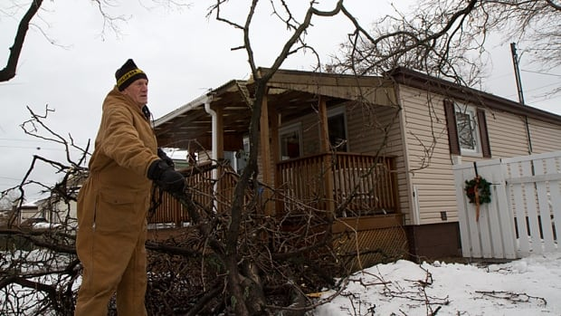 John McDonald is cleaning up three trees that fell in his yard during the ice storm. The branches damaged his back porch and possibly his roof.