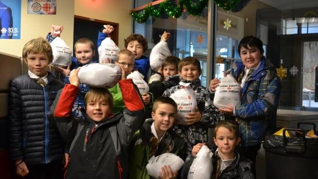 Students from the Holyrood School Choir donate turkeys, part of the record-setting haul of turkeys — and cash — that swooped in from generous Edmontonians for the CBC Turkey Drive.