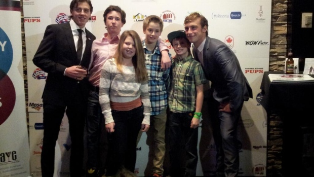 Mark McMorris (left) and Craig McMorris (right) pose with kids at their charity event in Regina.