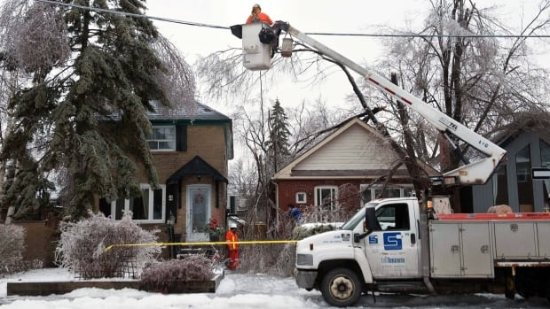 Workers from Stacey Electric, a Toronto Hydro subcontractor, work to repair downed power lines around Victoria Park and Denton Avenues in Scarborough, Monday, December 23, 2013, after a severe ice storm hit Toronto.