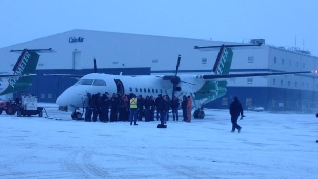 Hydro workers from Manitoba board a charter plane on Tuesday to head to Ontario and help restore power in the wake of the weekend's ice storm.