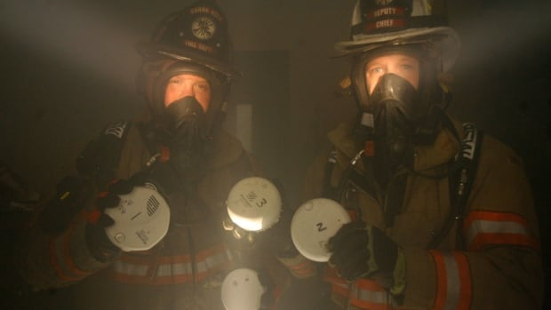Ionization smoke detectors, held by two U.S. firefighters in a smoke room in Barre, Vt., don't sound as early as photoelectric smoke detectors in smouldering, smoky fires.