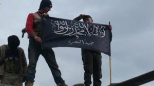 Rebels from the al-Qaeda affiliated group Jabhat al-Nusra, or the Nusra Front, wave their brigade flag as they step on top of a Syrian air force helicopter at Taftanaz air base in northern Syria, which was captured by anti-regime forces earlier this year. This photo is a citizen journalism image provided the by Edlib News Network and authenticated based on its contents and other reporting.
