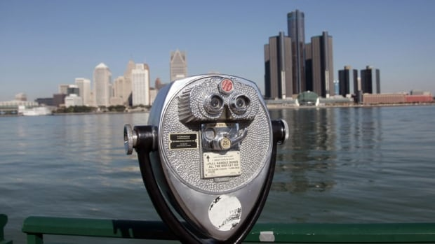 A viewing machine in Windsor overlooks the Detroit skyline. John Morillo was oblivious that helicopters and boats had been called into service to search for him as he swam across the river in