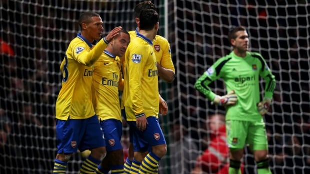 Theo Walcott of Arsenal, second left, celebrates with Kieran Gibbs, left, as he scores their first goal during the Premier League match between West Ham United and Arsenal at Boleyn Ground on Thursday in London, England.