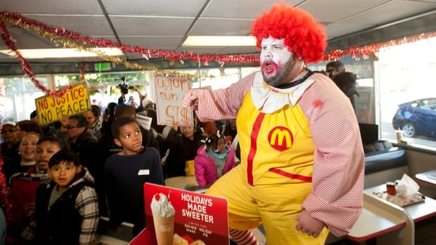 A demonstrator protests inside a McDonald's restaurant demanding higher wages for employees in California, Dec. 5. McDonald's has shut down a website that offered employees lifestyle tips, including sample budgets for that were based on holding two jobs.