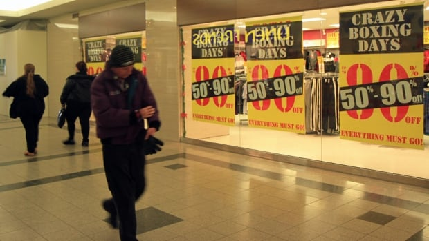 Shoppers walk past by sales banners at Jackson Square. The city's shopping malls saw steady traffic on Boxing Day, but many independent stores on Ottawa Street remain closed for the holiday.